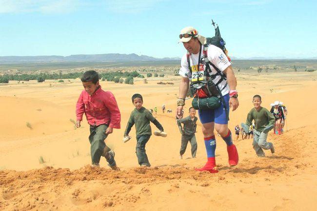 Учасника 24-го Піщаного марафону супроводжують діти через кілька хвилин після старту. Учасники підіймаються по першій піщаній дюні в 300 км на південь від Кварзазате в Марокко. У цьому році в марафоні взяло участь 812 чоловік. (AFP / Getty Images / Pierre Verdy)