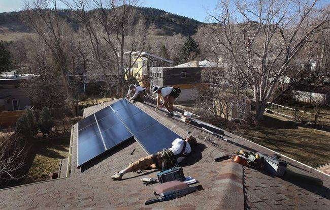 Працівники компанії «Namaste Solar» встановлюють сонячну панель на дах будинку 4 березня в Болдері, штат Колорадо. (Getty Images / John Moore)
