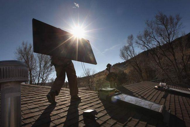 Уейд Ендрюс - працівник компанії «Namaste Solar» - несе сонячну панель на даху житлового будинку 4 березня в Болдері, штат Колорадо. Компанії з вироблення відновлюваної енергії (такі як «Namaste») отримають додаткові фонди на створення «зелених» ініціатив з федерального пакету економічних стимулів. (Getty Images / John Moore)