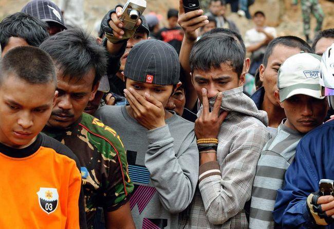 Жителі дивляться на те, як індонезійські солдати, поліція і місцеві жителі піднімають тіло жертви зсуву. Знімок зроблений в селі Pamoyanan в Сібінонге 3 вересня. (AFP / Getty Images / Adek Berry)